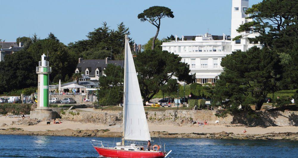 Voilier rouge navigant sur l'Odet face à la villa