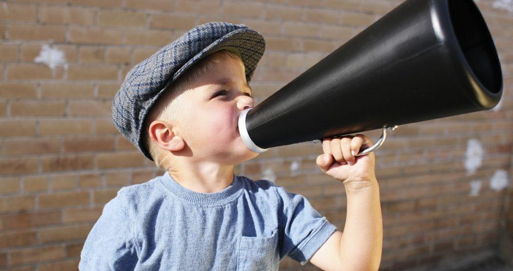 Petit garçon parlant dans un mégaphone, tel un crieur ou vendeur de journaux à une autre époque