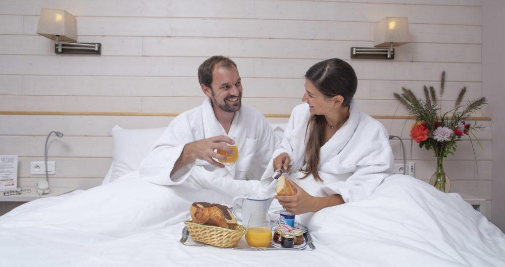 Couple prenant un petit-dejeuner au lit