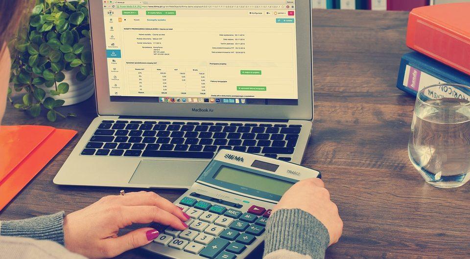 Une personne utilise une calculatrice à côté d'un ordinateur portable