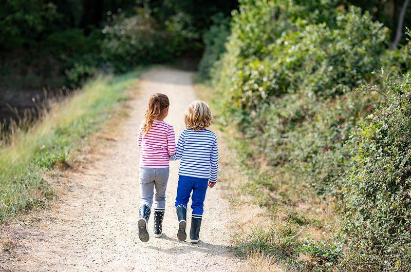 Deux enfants se promenant sur un chemin au bord d'une anse