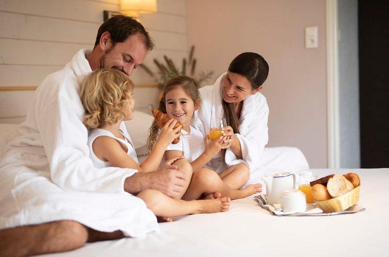 Famille assise sur le lit en prenant un petit déjeuner