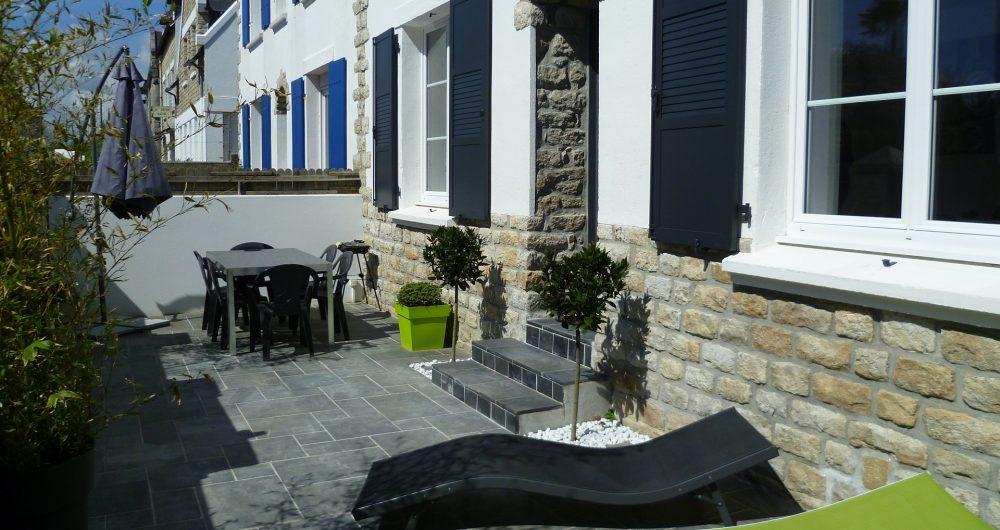 Vue d'une maison avec sa terrasse et des transats