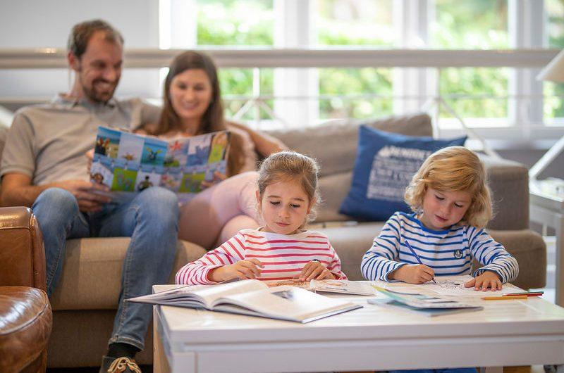 Famille lisant et jouant dans le salon