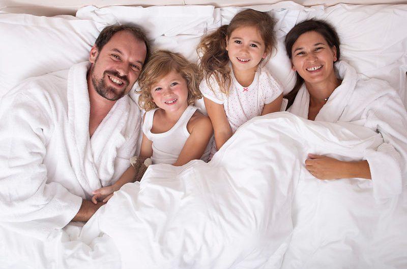 Une famille de quatre personnes dans un lit blanc