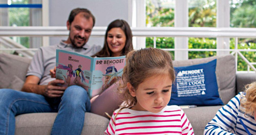 Couple lisant la brochure de Bénodet assis sur un canapé