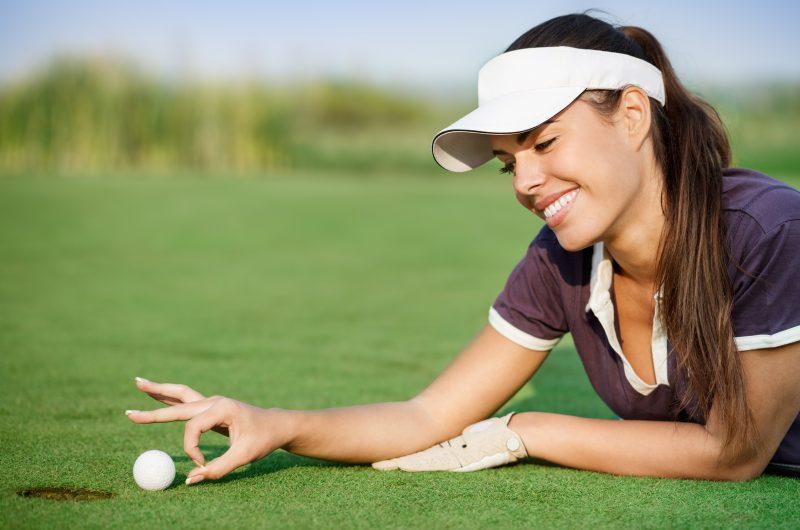 Woman pushing golf ball